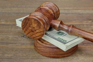 A Judge's Gavel On Top of a Stack of One Hundred Dollar Bills