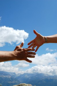 Photo of hands reaching, shaking, taking leap of faith